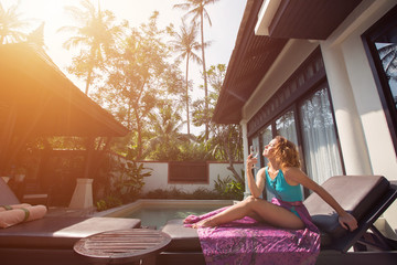 Young woman enjoy sun and summer sitting on chaise-lounge near swimming pool luxury villa hotel
