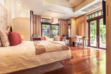 Luxury bedroom hotel interior, big window, terrace, sofa, wooden floor