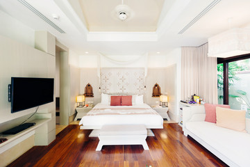 Luxury bedroom hotel interior, TV, sofa, wooden floor