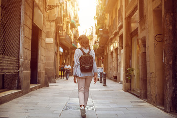 Traveling female walking on  European city street, tourism in Europe, travel background