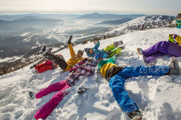 Group of happy friends having fun and Lying in snow. Ski and snowboard holiday