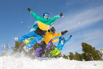 Group of happy friends having fun jumping to snow. Ski and snowboard holiday