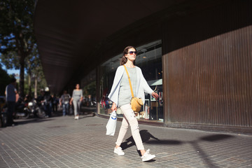 Beautiful woman walking on City street with bags after  shopping. Sunny summer day