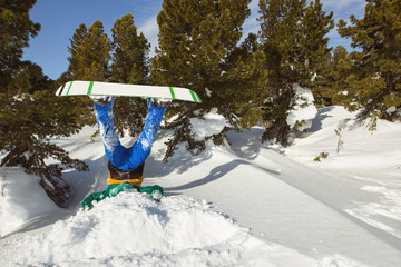 Snowboarder upside down in snow in winter Pines forest
