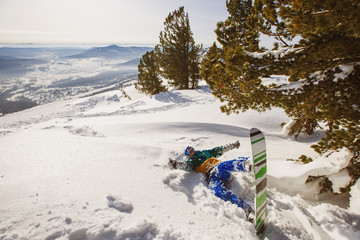 Snowboarder lying down in snow in winter Pines forest