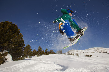 Snowboarder jumping through air in winter forest and snow