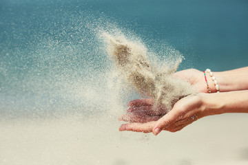 Female hands releasing dropping sand. Sand flowing through the hands against blue ocean