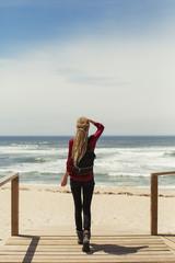 Young woman wearing dreadlocks walking down pier to Atlantic Ocean. Summer travel in Europe