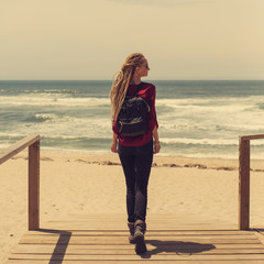 Young woman wearing dreadlocks walking down pier to Atlantic Ocean. Summer travel in Europe, Portugal