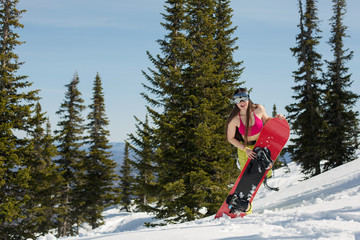 Portrait of smiling snowboarder female in winter mountain forest. Sunny winter holiday, winter sport outdoor