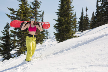 Portrait of young snowboarder female going to freeride in winter mountain forest. Sunny winter holiday, winter sport outdoor