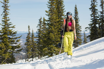 Portrait of snowboarder female walking in winter mountain forest with snowboard. Sunny winter holiday, winter sport outdoor
