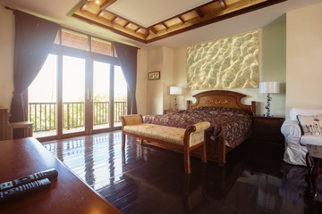 Luxury villa bedroom interior, wooden floor, big windows and balcony