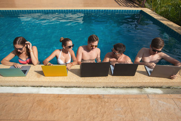 Group of people freelancers using laptop computer sitting in swimming pool and work together