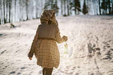 Girl walking in winter forest holding lamp in her hand