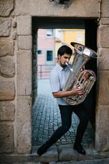 Street musician playing tuba outdoor in European city