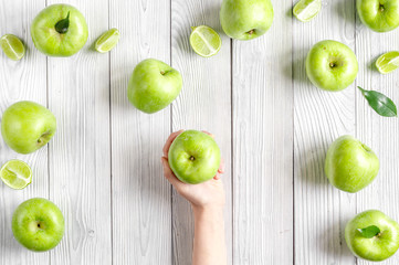 natural food design with green apples in hands white desk background top view
