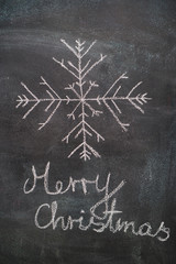 Big snowflake with Merry Christmas writing drawn with white chalk on blackboard