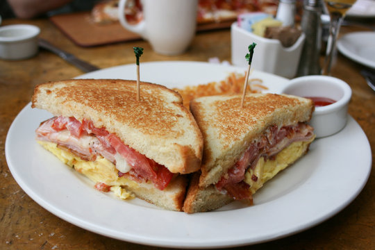 Eggs, bacon and cheese breakfast sandwich with hash brown potatoes, close up, lifestyle, horizontal