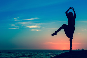 Silhouette of flexible girl on the sea coast during a amazing sunset.