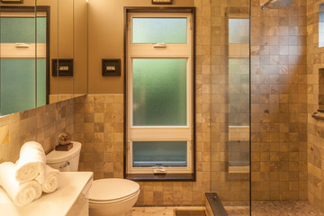 modern tan bathroom with tiled wall and walk in shower
