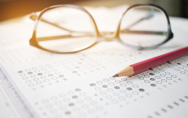 optical form of an examination with pencil and glasses, filling a standardized exam test form in school, vintage tone