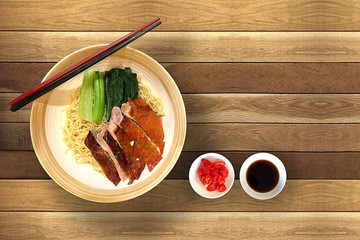 Delicious and popular Chinese food of Dry egg noodle with roast duck and fresh green vegetable.