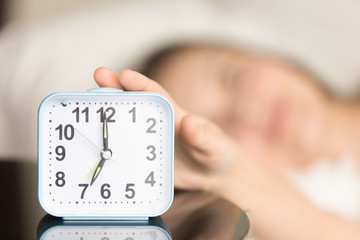 Close up picture of square alarm clock on bedside table showing seven o'clock AM with blurred person in bed reaching hand to turn off the awake signal sound. Waking up for work in morning concept