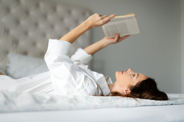 Young woman at home on bed reading book