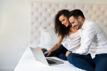 Cheerful young couple looking together at laptop