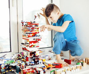 little cute preschooler boy playing lego toys at home happy smil