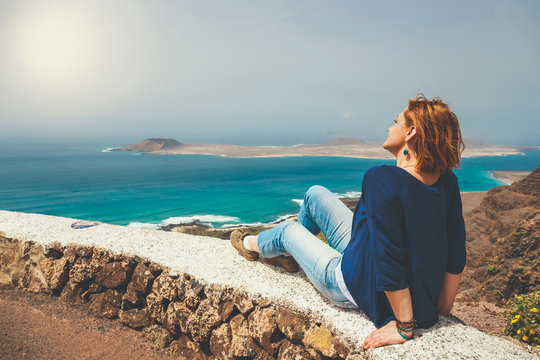Young woman sitting on stone fence looking at sea