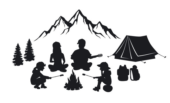 Family sit around campfire silhouette scene with mountains, tent and pine trees. People camping outdoor