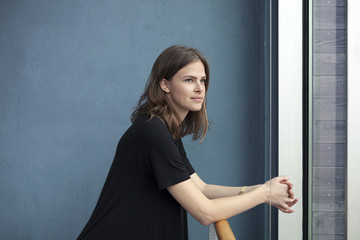 Portrait of a brunette girl infront of a blue wall