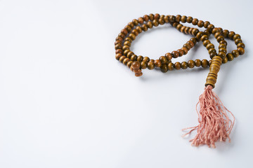 Muslim wooden rosary beads isolated on white background with copy space. Ramadan concept.