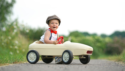 spielender Junge lacht im Tretauto