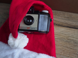 Santa Claus hat with camera on wood backgroun