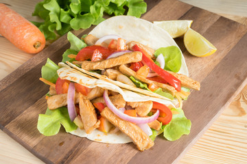 Grilled meat with onion and bell peppers, tomato,lettuce and serve with flour tortilla on wooden board.