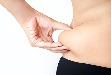 Woman measuring her belly fat with her hands, close up
