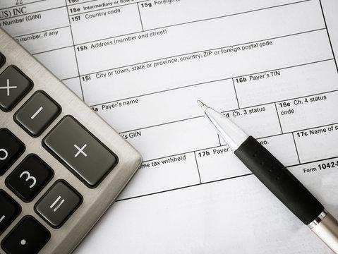 Top view calculator with pen on Tax Season: 1042 U.S. Individual Income Tax Return