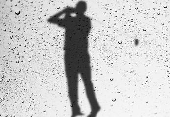 glass window wih raindrops as it looks a golfer