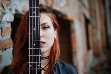 Red haired punk girl wear on black with bass guitar at abadoned place. Portrait of gothic woman musician. Close up face of blackness person with guitar riff.