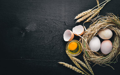 Chicken eggs in the nest. Wooden photo on a black background. Top view. Free space.