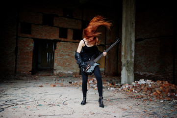 Red haired punk girl wear on black with bass guitar at abadoned place. Portrait of gothic woman musician.