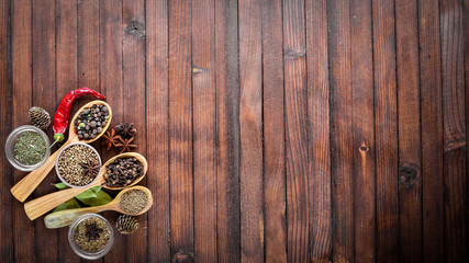 A mixture of spices. Wooden spoon. On Wooden background. Top view.