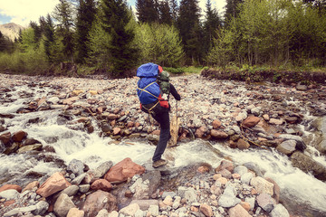 Man traveler with backpack crosses a mountain river. Vintage image