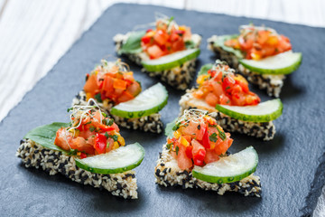 Appetizer canape with chopped vegetables and sesame on stone slate background close up. Delicious snacks, sandwiches, crostini, bruschetta, antipasti on party or picnic time. Top view
