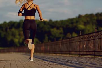 Girl runner jogging in the park in morning  evening.