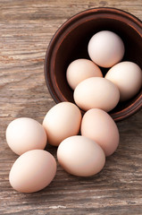 uncooked brown hen eggs on wooden table close-up