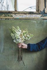 Junge hält selbst gepflückte Blumen in der Hand
